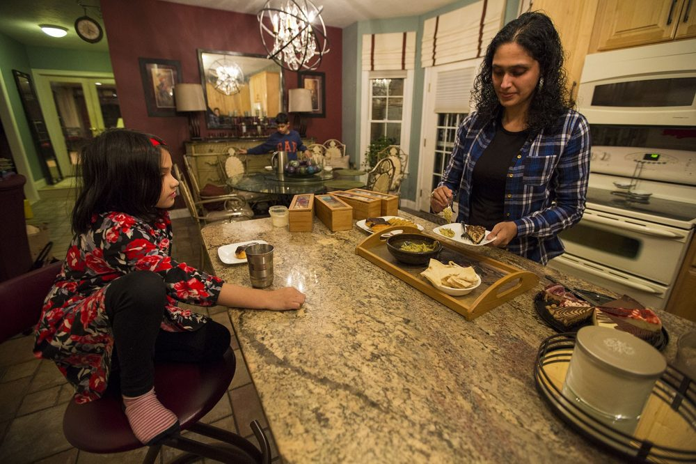 Asima Silva prepares snacks for her family at their home. (Jesse Costa/WBUR)