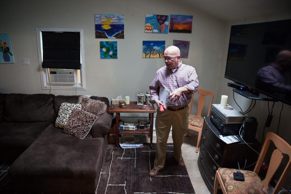 Ken Aligata walks through an inspection of Right Path House in Clinton, Conn. Artwork made by residents during therapy sessions hangs on the wall behind him. (Ryan Caron King/WNPR)