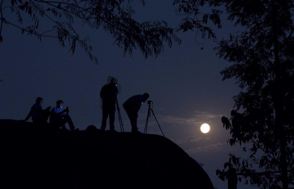 Tourists take photographs of the rising moon in Gauhati, India, Monday, Nov. 14, 2016. (Anupam Nath/AP)