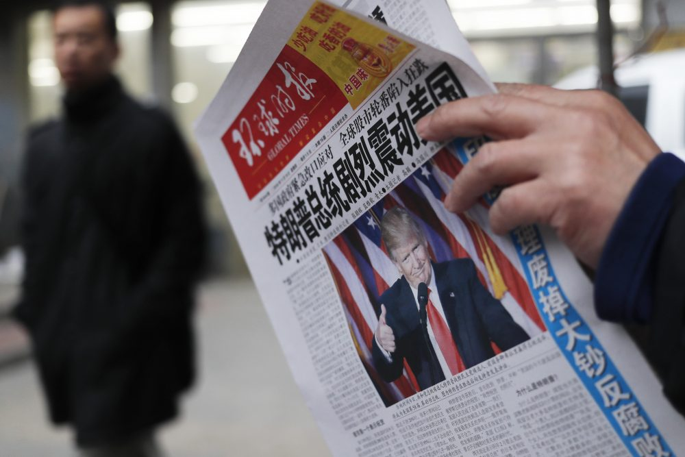 "A man reads a newspaper with the headline of ""U.S. President-elect Donald Trump delivers a mighty shock to America"" at a news stand in Beijing on Nov. 10, 2016. (Andy Wong/AP)"