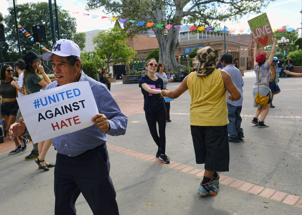 """A man carrying a sign that reads """"United Against Hate"""" dances with other demonstrators during a demonstration against presidential elect Donald Trump in Oliveira Plaza in downtown Los Angeles on Saturday, Nov. 12, 2016. (Richard Vogel/AP)"""