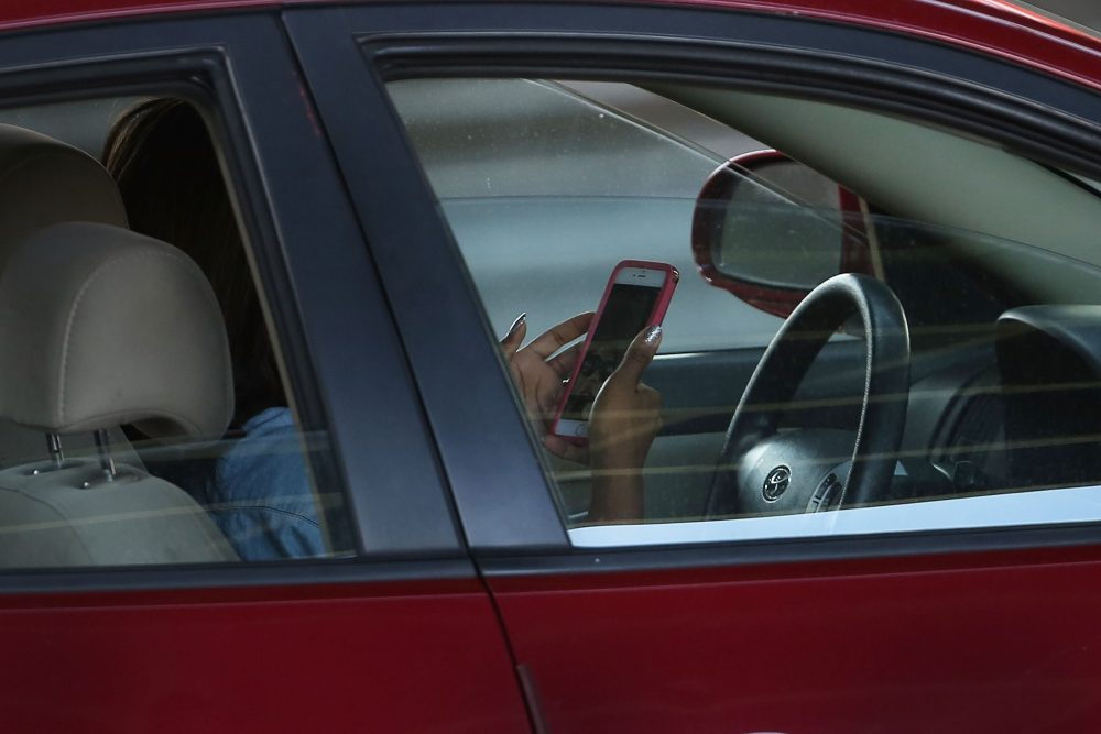 A driver uses a phone while behind the wheel of a car in New York in April 2016. (Spencer Platt/Getty Images)