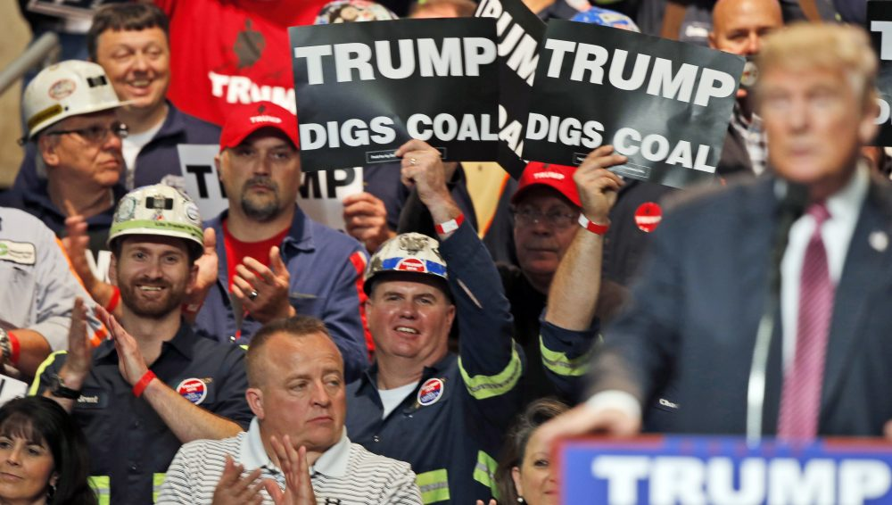 In this May 5, 2016 photo, coal miners wave signs as Republican presidential candidate Donald Trump speaks during a rally in Charleston, W.Va. (Steve Helber/AP)