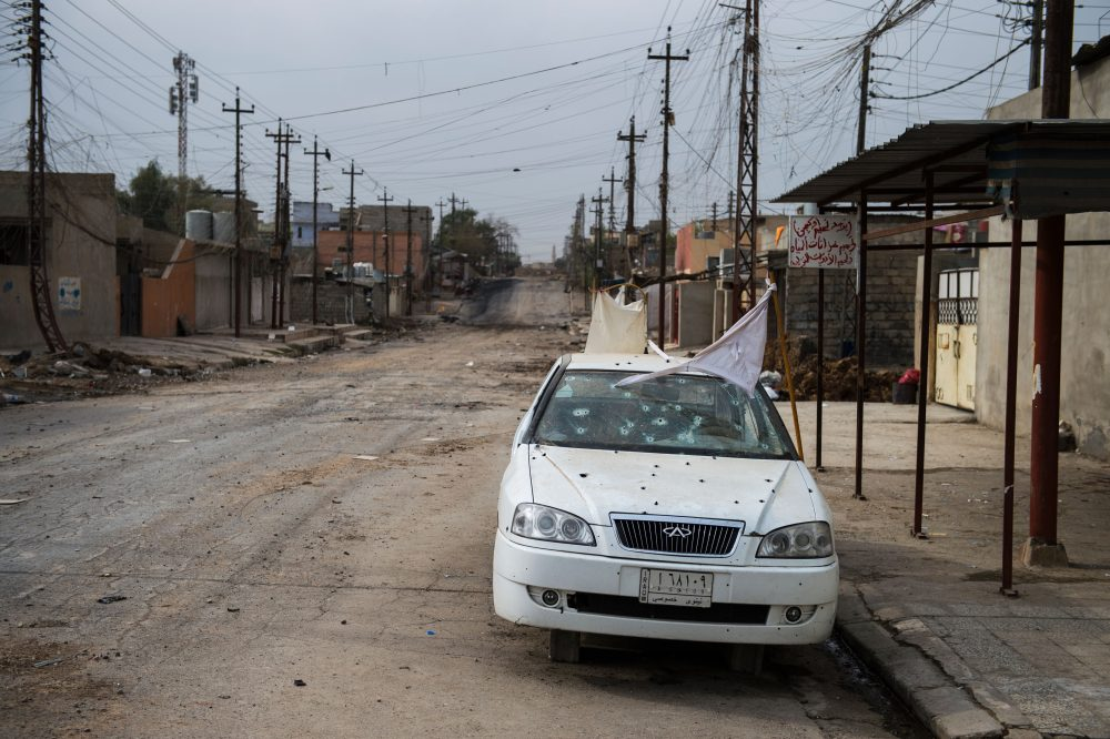 A white flag is seen on a bullet ridden car in a deserted street in the Aden neighbourhood in Mosul, Iraq, on Nov. 16, 2016. Iraqi forces are fighting to take back control of the city from ISIS. (Odd Andersen/AFP/Getty Images)