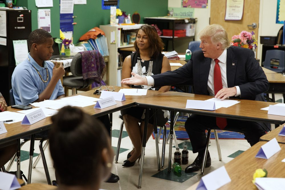 In this Sept. 8, 2016, file photo, then-Republican presidential candidate Donald Trump reaches to shake hands with Egunjobi Songofunmi during a meeting with students and educators before a speech on school choice at Cleveland Arts and Social Sciences Academy in Cleveland. School voucher programs in the nation's capital and Vice President-elect Mike Pence's home state of Indiana could serve as a blueprint for a Trump administration education plan. (Evan Vucci/AP, File)