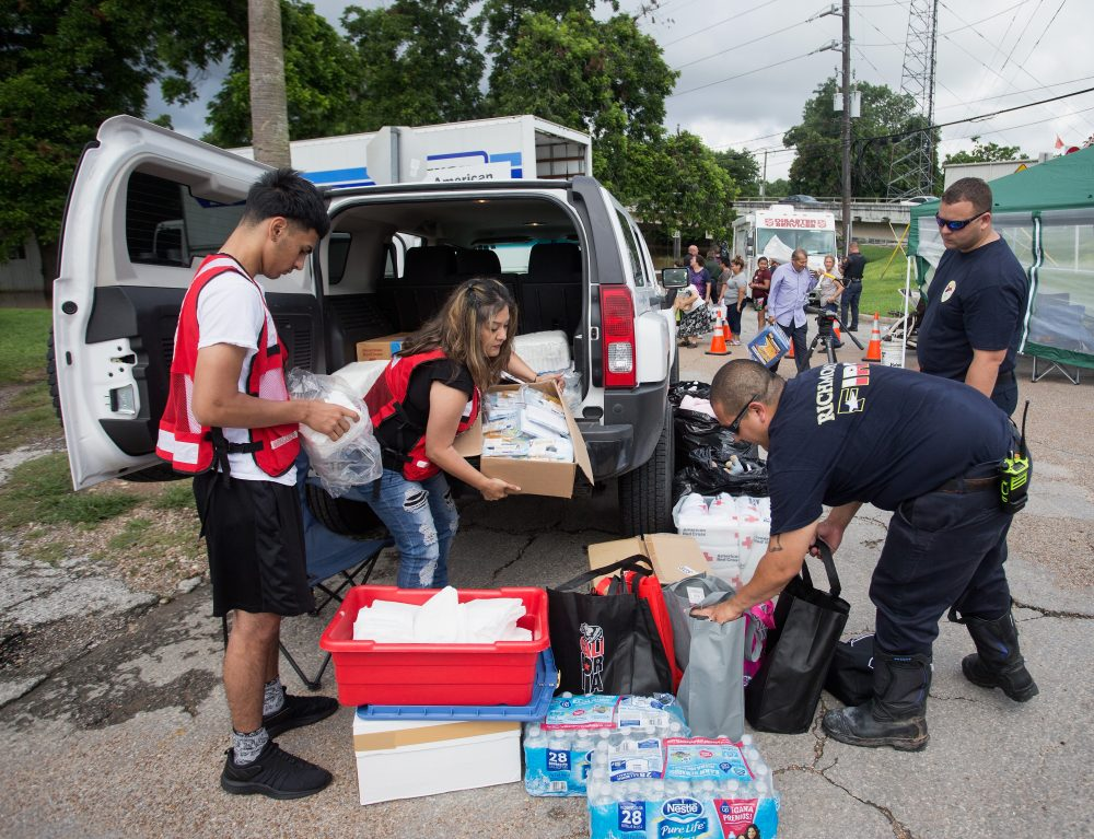 Members of the American Red Cross along with Gabe Escochea and Brett Hafer of the Richmond Fire Department prepare items for flood stricken families along the Brazos River in Richmond, Texas, in June 2016. (Bob Levey/Getty Images)