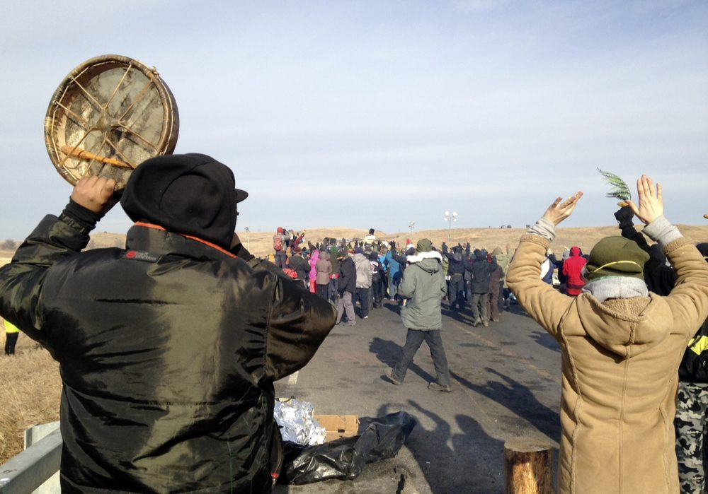 Protesters against the Dakota Access oil pipeline congregate Monday, Nov. 21, 2016, near Cannon Ball, N.D., on a long-closed bridge on a state highway near their camp in southern North Dakota. (James MacPherson/AP)