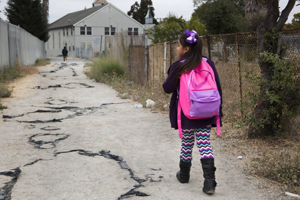 Celia Fragoso, 7, walks through the Oakland neighborhood of Sobrante Park on her way to Madison Park Academy on Aug. 26, 2016. (Brittany Hosea-Small/KQED)