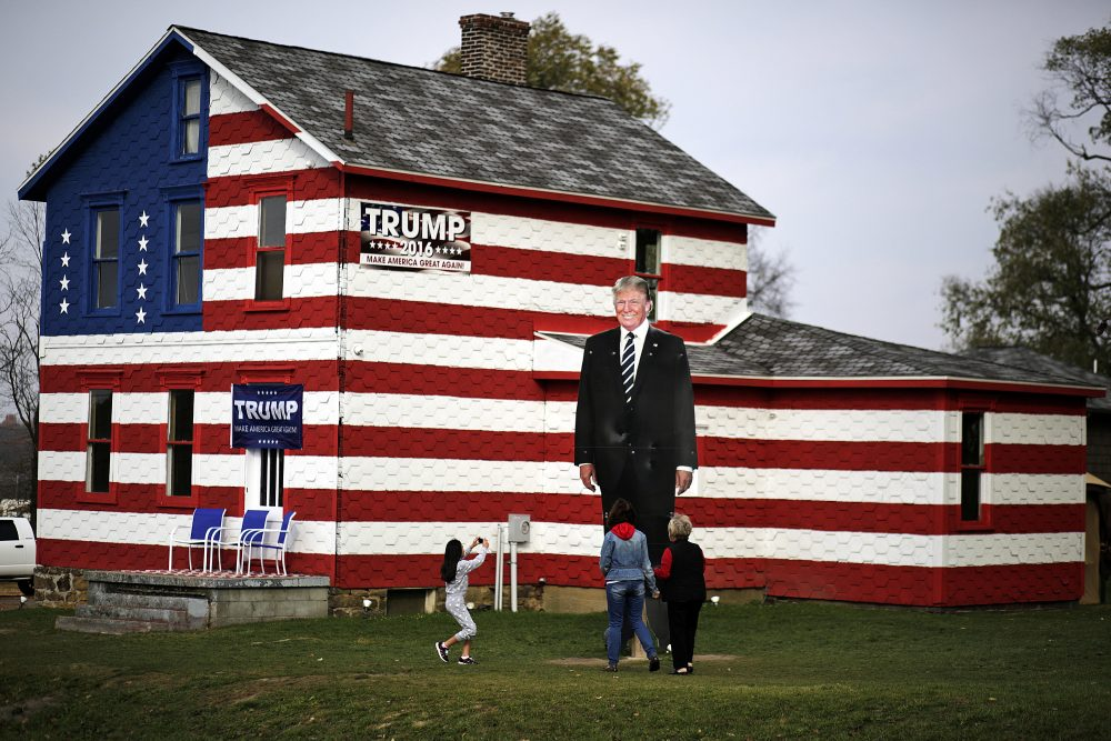 A young visitor takes a photo of a giant cutout of Republican candidate for president Donald Trump in front of the Trump House owned by Lisa Rossi in Youngstown, Pa, Tuesday, Nov. 8, 2016. (Gene J. Puskar/AP)