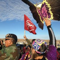 In these times, writes Frederick Hewett, social justice groups need to seek out linkages between their respective missions...even if it means other causes may momentarily overshadow their own. Pictured: Demonstrators against the Dakota Access oil pipeline hold a ceremony at the main protest camp Tuesday, Nov. 15, 2016, near Cannon Ball, North Dakota. (James MacPherson/AP)