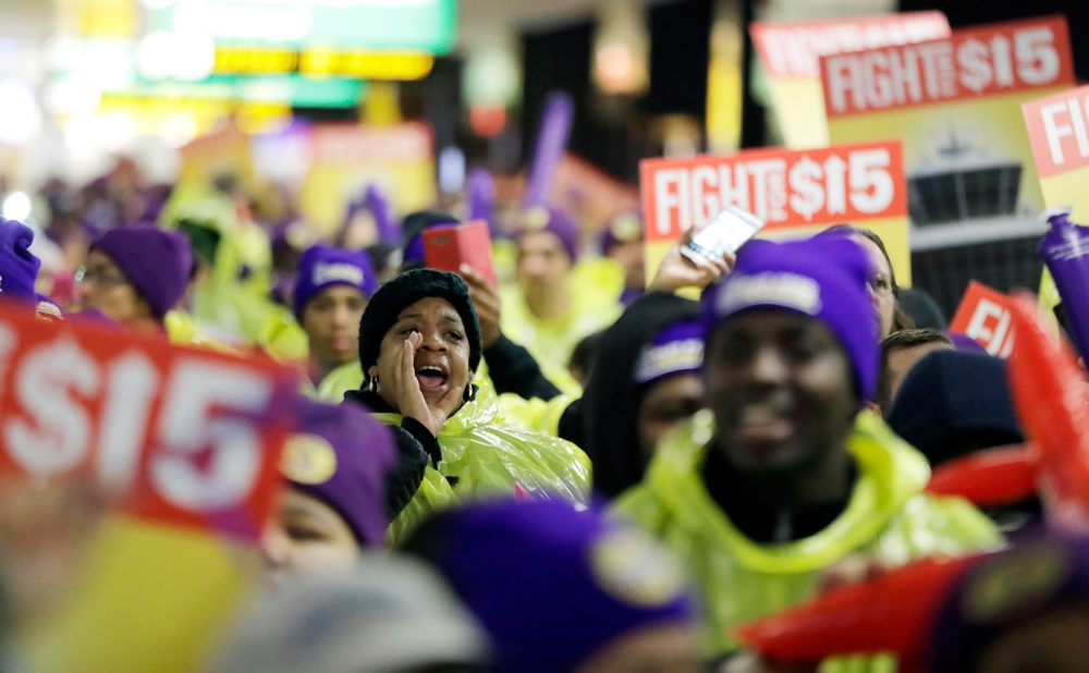 A woman shouts while marching with service workers asking for $15 minimum wage pay during a rally at Newark Liberty International Airport on Tuesday. (Julio Cortez/AP)