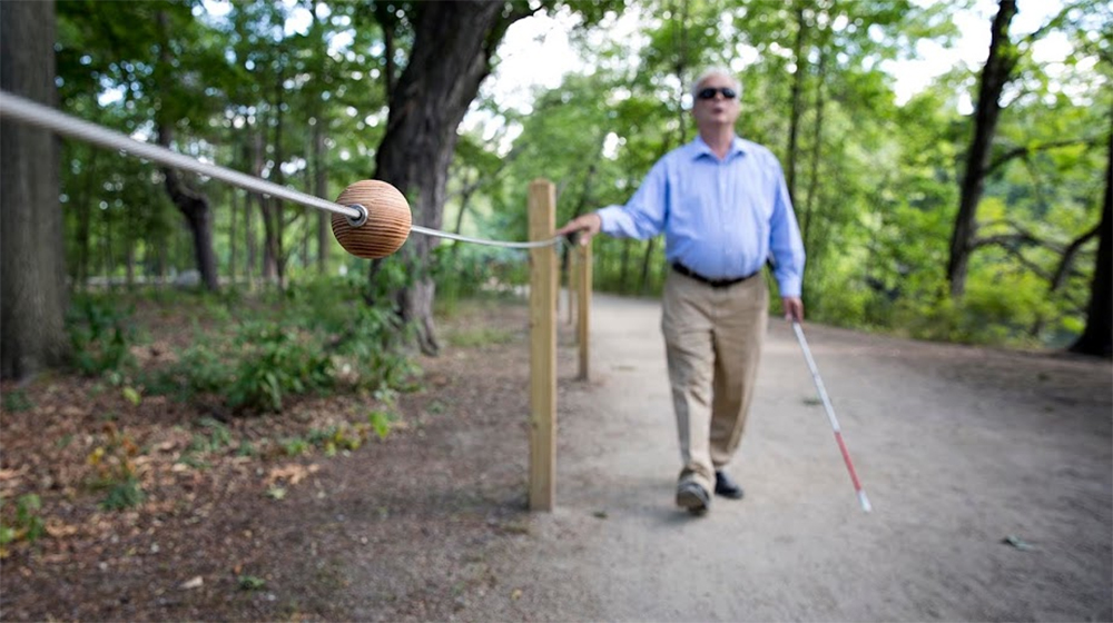 Following a cable along the braille trail in Watertown, Jerry Berrier, 64, approaches a spherical block, which will tell him that there's a bench on the opposite side of the trail. (Robin Lubbock/WBUR)