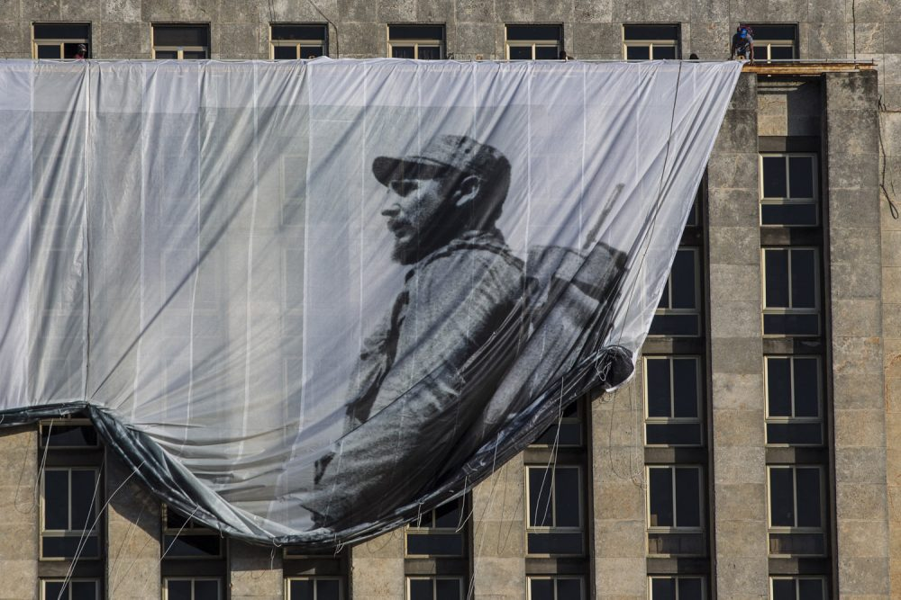 Men hang a giant banner with a picture of Cuba's late leader Fidel Castro as a young revolutionary, from the Cuban National Library building in Havana, Cuba. (Desmond Boylan/AP)
