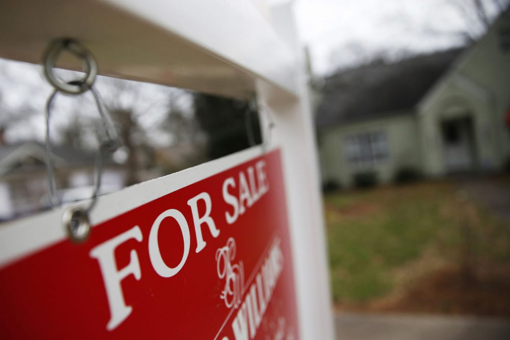 "This Jan. 26, 2016 file photo shows a ""For Sale"" sign hanging in front of an existing home in Atlanta. (John Bazemore/AP)"