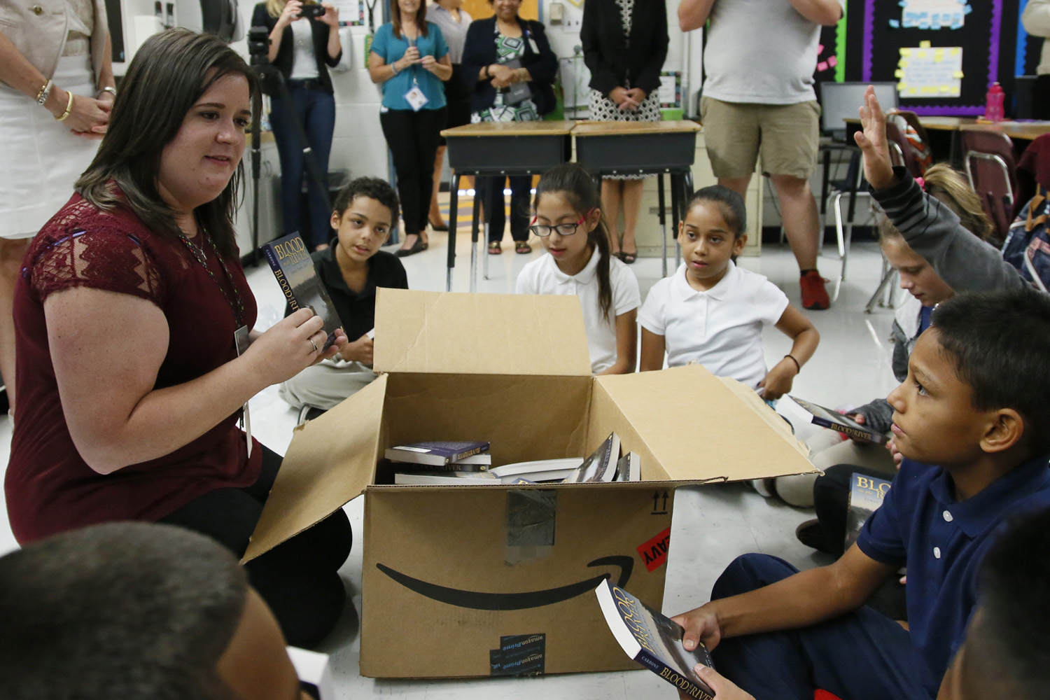 Monta Johnson, left, a fifth-grade teacher at Adams Elementary School, passes out books to her class in Oklahoma City. (Sue Ogrocki/AP)