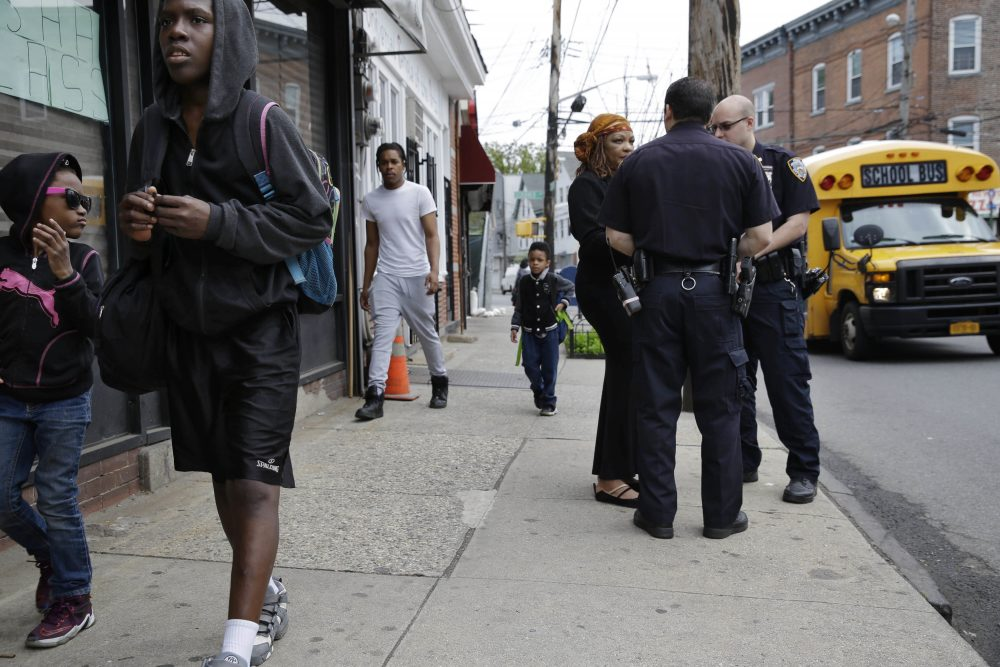 Police officers talk with a community activist in New York on May 24, following deaths of black men in encounters with police in Minnesota, Louisiana and across the country, and the sniper killing of five Dallas officers. (Seth Wenig/AP)