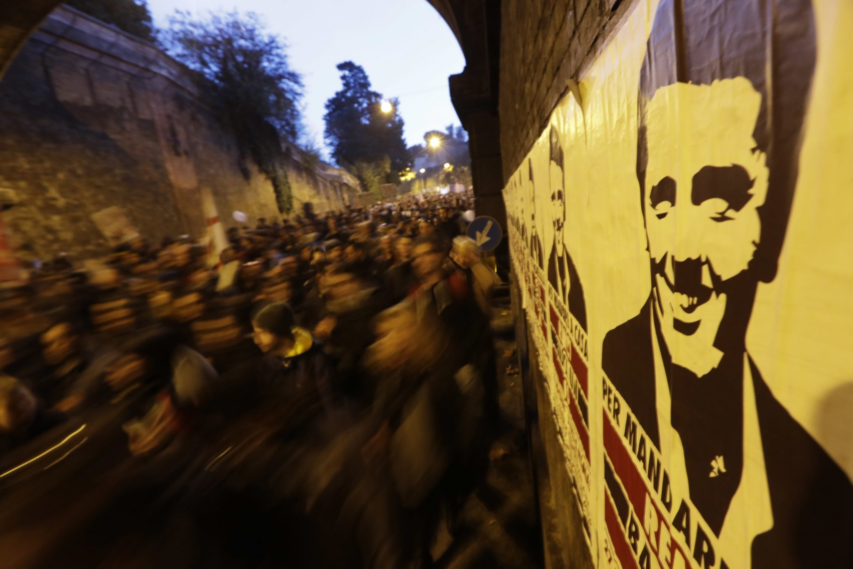 Protesters march past a poster depicting Italian Premier Matteo Renzi during a demonstration ahead of a referendum over a constitutional reform, in Rome, Sunday, Nov. 27, 2016. (Andrew Medichini/AP)