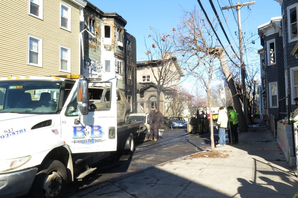 The view on Berkshire Street in East Cambridge Sunday afternoon as crews started cleaning up from Saturday's 10-alarm fire. (Simón Rios/WBUR)