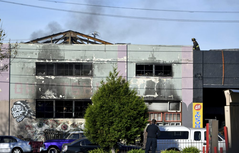 A firefighter walks on the roof of a smoldering building after a fire tore through a warehouse party early Saturday, Dec. 3, 2016 in Oakland. (Josh Edelson/AP)