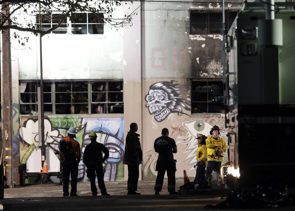 Emergency personnel stage in front of the site of a warehouse fire that started Friday night and killed dozens, Sunday, Dec. 4, 2016, in Oakland, Calif. (Marcio Jose Sanchez/AP)