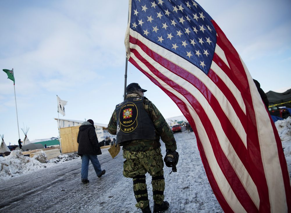 Navy veteran Rob McHaney, of Reno, N.V., walks with an American flag at the Oceti Sakowin camp where people have gathered to protest the Dakota Access oil pipeline in Cannon Ball, N.D., Sunday, Dec. 4, 2016. (David Goldman/AP)