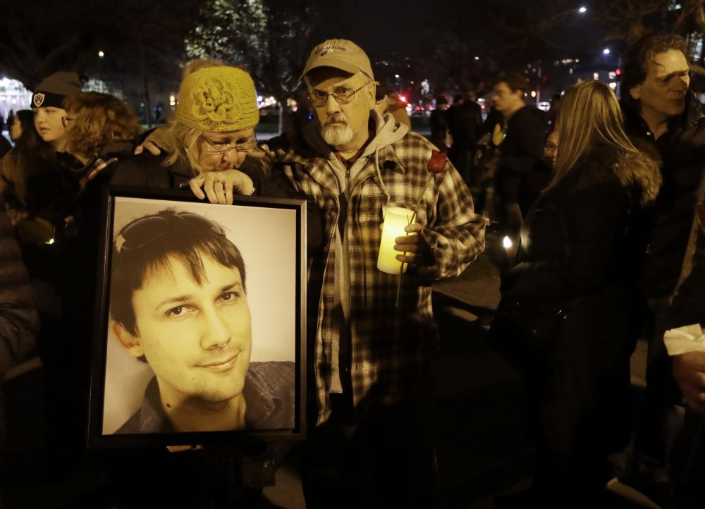 Judy Hough, left, and her husband Brian, center, hold a picture of their son Travis, who died in a warehouse fire, during a vigil at Lake Merritt on Monday, Dec. 5, 2016, in Oakland, Calif. (Marcio Jose Sanchez/AP)