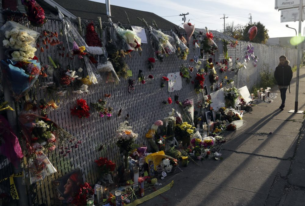 Flowers, pictures and candles adorn a fence at a makeshift memorial near the site of the warehouse fire in Oakland, California. (Marcio Jose Sanchez/AP)
