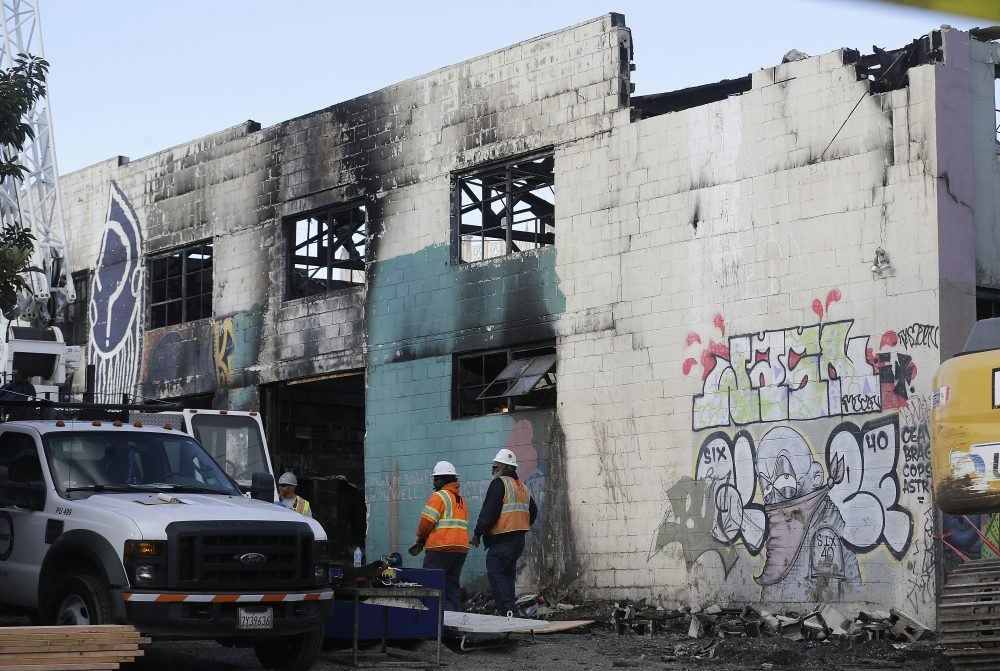 Emergency crew workers walk in front of the site of a warehouse fire in Oakland, Calif., Tuesday, Dec. 6, 2016. The fire erupted Friday, Dec. 2, killing dozens. (Jeff Chiu/AP)