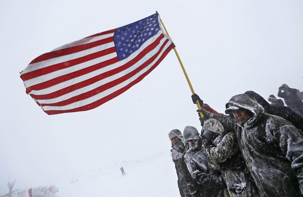 Military veterans huddle together to hold an American flag against strong winds during a march to a closed bridge outside the Oceti Sakowin camp where people have gathered to protest the Dakota Access oil pipeline in Cannon Ball, N.D., Monday, Dec. 5, 2016. (David Goldman/AP)