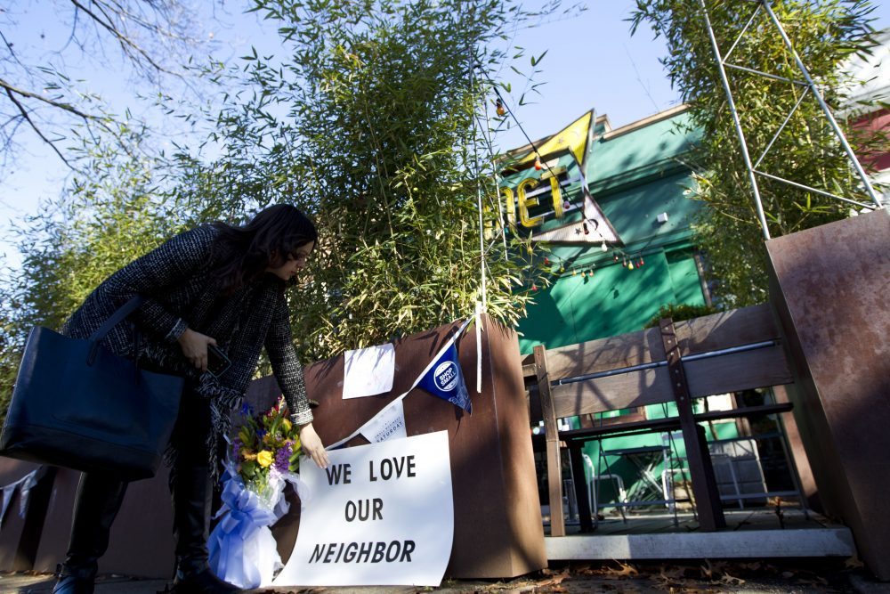 """Meighan Stone places a support banner with flowers outside the door of Comet Ping Pong pizza shop, in Washington, Monday, Dec. 5, 2016. A fake news story prompted a man to fire a rifle inside the popular Washington, D.C., pizza place as he attempted to """"self-investigate"""" a conspiracy theory that Hillary Clinton was running a child sex ring from there, police said.  (Jose Luis Magana/AP)"""