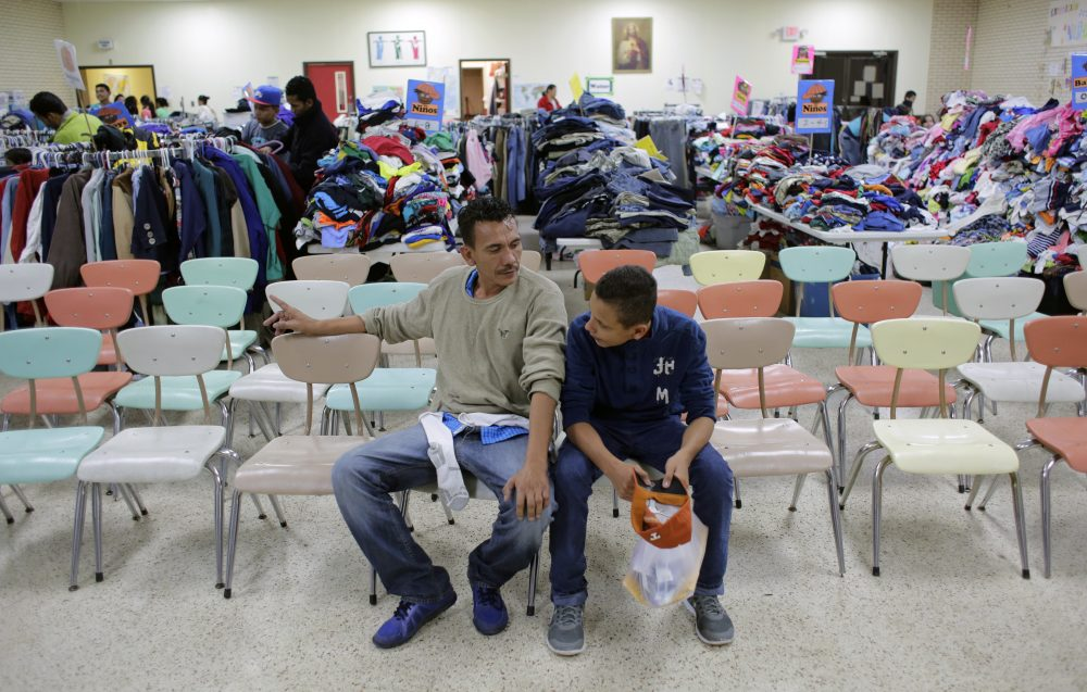 Roger Mesa, right, a 15-year-old from Honduras who is headed to Miami with his father, Luis Carlos, a construction worker, left, sit at the Sacred Heart Community Center in the Rio Grande Valley border city of McAllen, Texas, Sunday, Nov. 13, 2016, after they were released after processing by U.S. Customs and Border Patrol. (Eric Gay/AP)