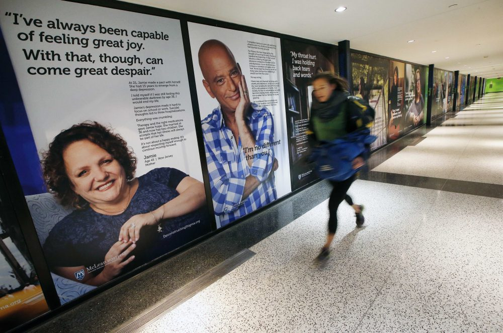 A passenger rushes past a new art exhibit at Logan Airport that consists of larger-than-life posters of nearly three dozen people who have struggled with mental illness. (Michael Dwyer/AP)