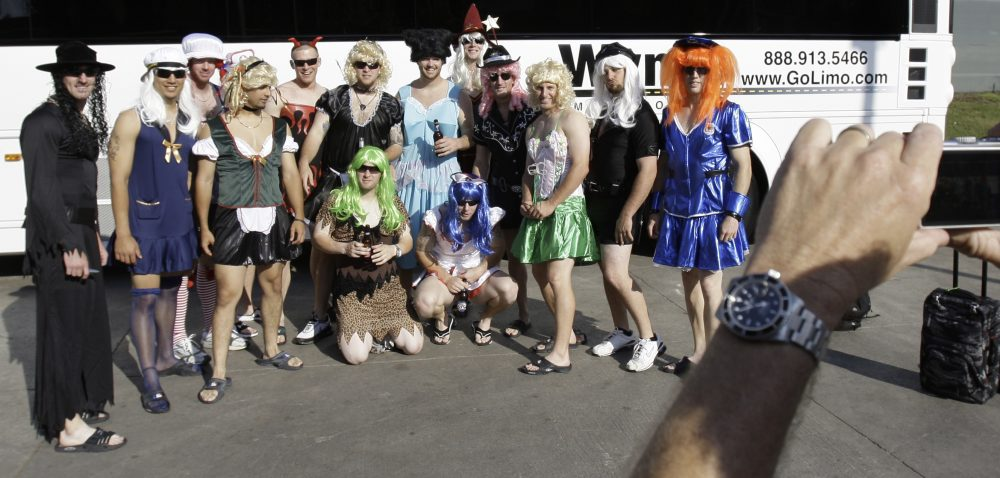 In this Sept. 24, 2008, file photo, Oakland Athletics rookie players dressed in costumes line up for a photo before boarding the team bus after their 14-4 loss to the Texas Rangers, in Arlington, Texas. That hazing ritual of dressing up rookies as Wonder Woman, Hooters Girls and Dallas Cowboys cheerleaders is now banned. (LM Otero/AP)