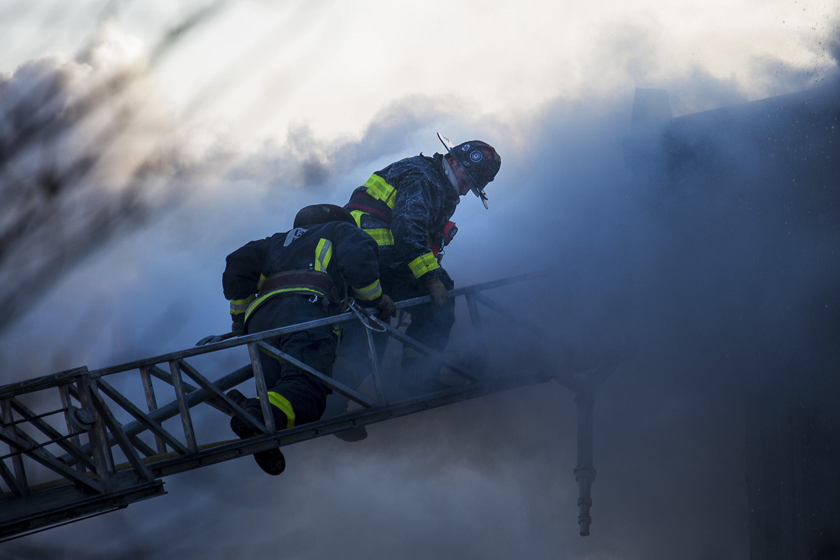 Boston firefighters battle the smoke of a smoldering fire on Bunker Hill Street in Charlestown. (Jesse Costa/WBUR)