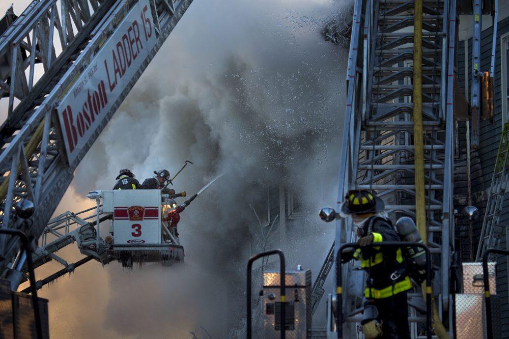 Boston firefighters battle a smoldering fire on Bunker Hill Street in Charlestown. (Jesse Costa/WBUR)