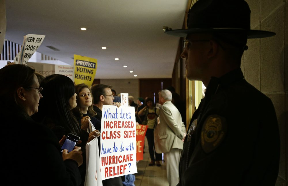 Demonstrators gather outside of a press conference room during a special session at the North Carolina Legislature in Raleigh, N.C., Thursday, Dec. 15, 2016. (Gerry Broome/AP)