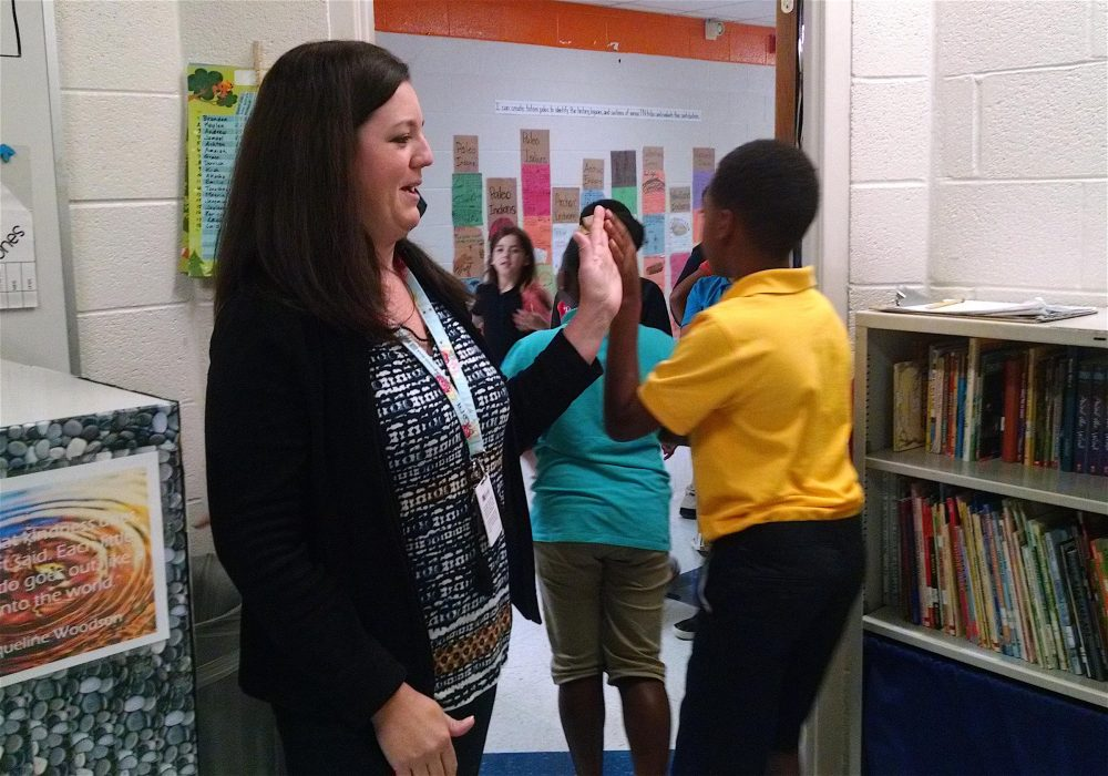 Jennifer Burnell high-fives students as they leave her classroom at Fall-Hamilton Elementary School. (Chas Sisk/WPLN)