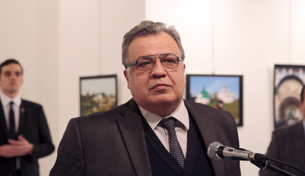The Russian Ambassador to Turkey Andrei Karlov speaks a gallery in Ankara Monday Dec. 19, 2016. A gunman opened fire on and killed Russia's ambassador to Turkey Karlov at a photo exhibition on Monday. The gunman is seen at rear on the left. (Burhan Ozbilici/AP)