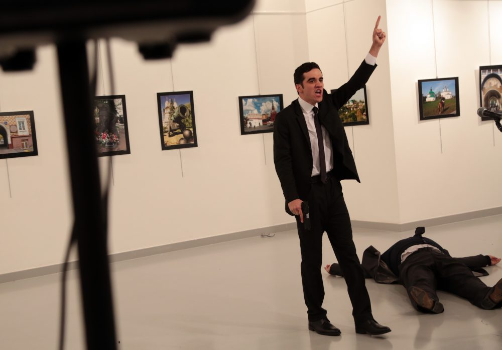 An unnamed gunman gestures after shooting the Russian Ambassador to Turkey, Andrei Karlov, at a photo gallery in Ankara, Turkey, Monday, Dec. 19, 2016. A Russian official says that the country's ambassador to Turkey has died after being shot by a gunman in Ankara. (Burhan Ozbilici/AP)