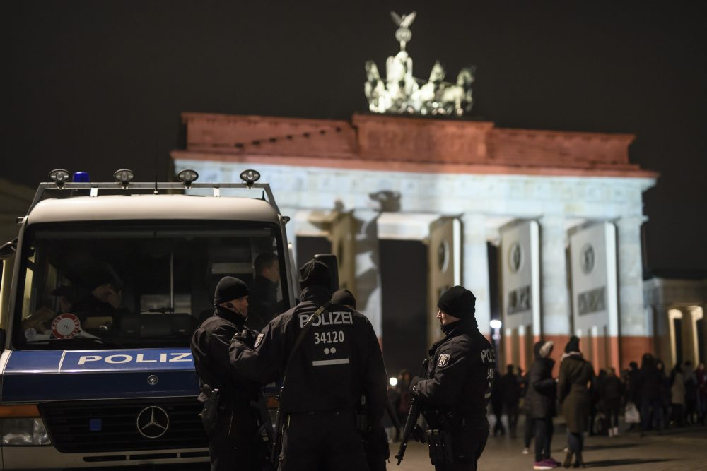 Policemen stand in front of the Brandenburg Gate with the colors of Berlin's flag in Berlin on Dec. 20, 2016 one day after a truck crashed into a Christmas market. (Clemens Bilan/AFP/Getty Images)