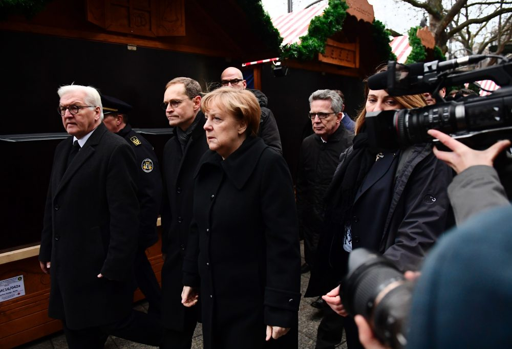 """German Chancellor Angela Merkel (C), German Foreign Minister Frank-Walter Steinmeier (L), German Interior Minister Thomas de Maiziere (4thL) and Berlin's mayor Michael Mueller (2ndL) walk through the Christmas market of the Kaiser-Wilhelm-Gedaechtniskirche (Kaiser Wilhelm Memorial Church), the day after an attack at the nearby Christmas market in central Berlin, on Dec. 20, 2016. German police said they were treating as """"a probable terrorist attack"""" the killing of 12 people when the speeding lorry cut a bloody swath through the packed Berlin Christmas market. (Tobias Schwarz/AFP/Getty Images)"""
