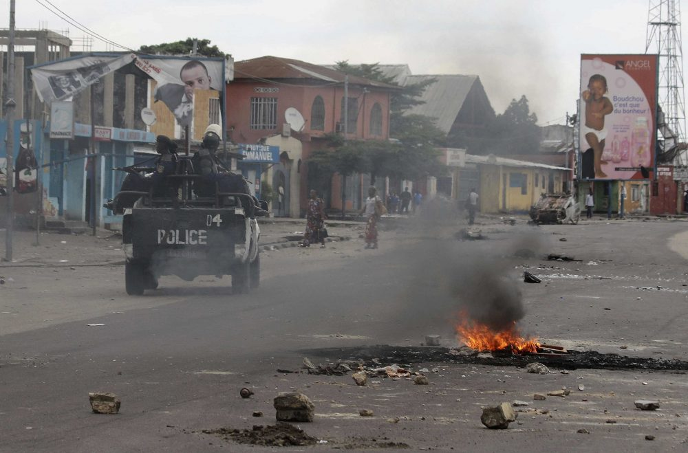 Policemen drive past burning debris during protests in Kinshasa, Democratic Republic of Congo, Tuesday, Dec. 20, 2016. (John Bompengo/AP)