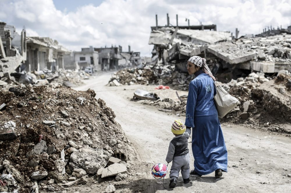 A Kurdish Syrian woman walks with her child past the ruins of the town of Kobane, also known as Ain al-Arab, on March 25, 2015. (Yasin Akgul/AFP/Getty Images)