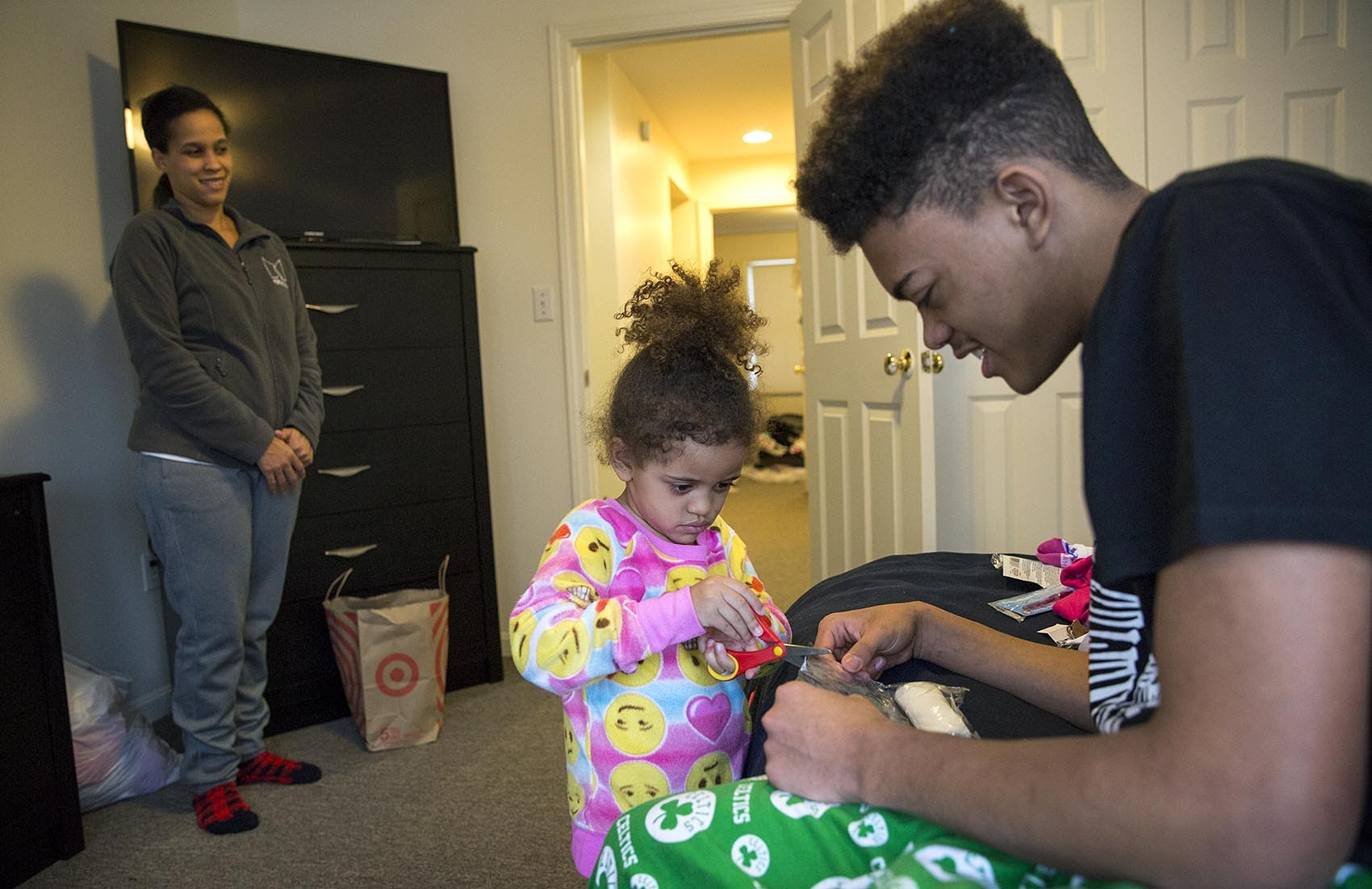 Settling into their new home, Isaiah Robinson, 16, plays with his sister Juliah, 3, as their mother, Heather, looks on. (Robin Lubbock/WBUR)