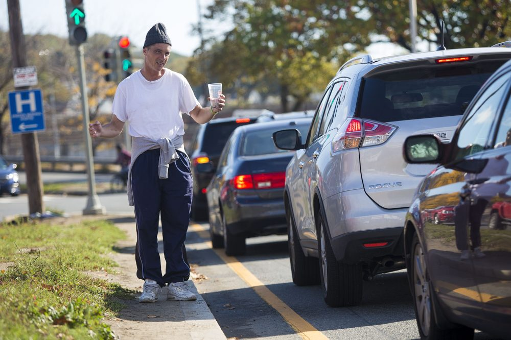 A man panhandles on Revere Beach Parkway in Everett in October. (Jesse Costa/WBUR)