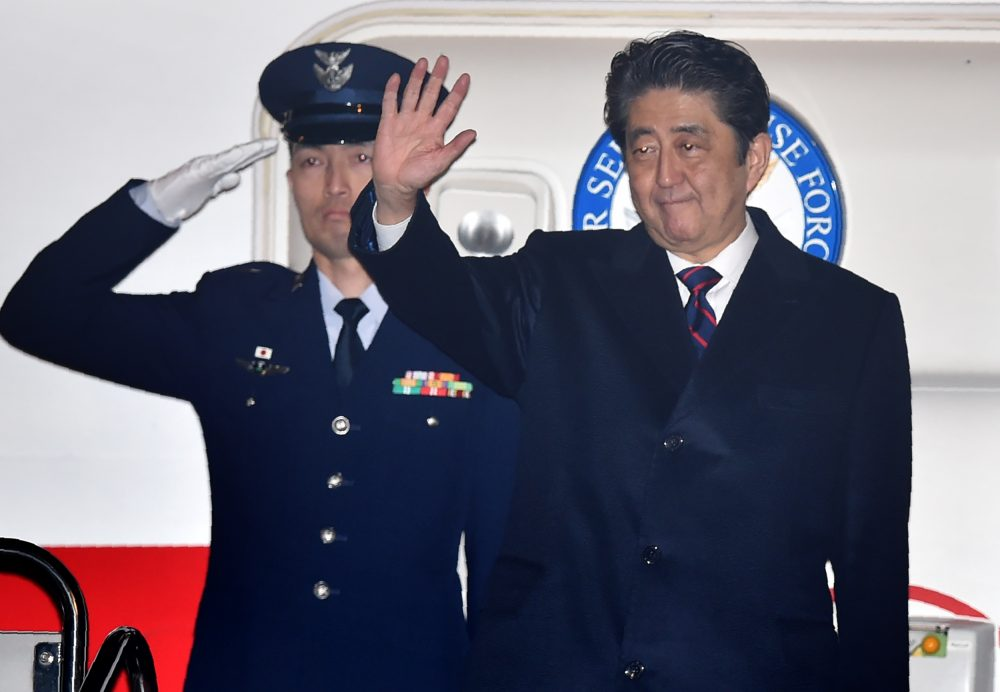 Japan's Prime Minister Shinzo Abe (right) waves before departure for Hawaii at Tokyo's Haneda airport on Dec. 26, 2016. (Kazuhiro Nogi/AFP/Getty Images)