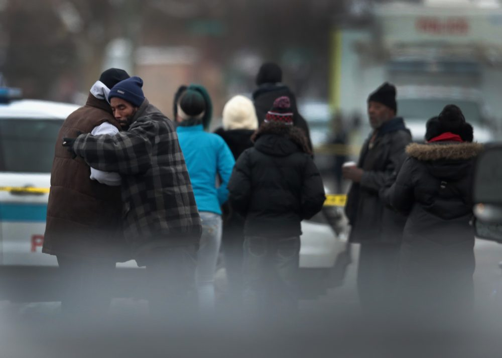 Friends, family and neighbors watch as police investigate the scene of a quadruple homicide on the South Side of Chicago on Dec. 17, 2016. (Scott Olson/Getty Images)