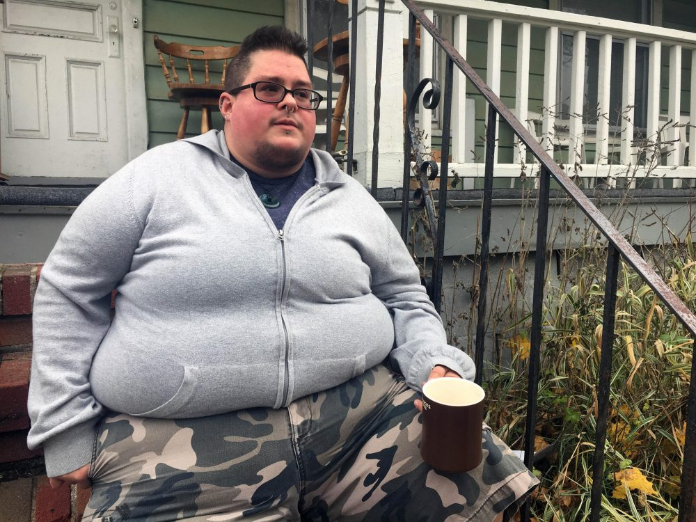 A Rochester, N.Y., native sits on his porch right before going to a name and gender change legal clinic hosted by the Empire Justice Center. (Karen Shakerdge/WXXI)