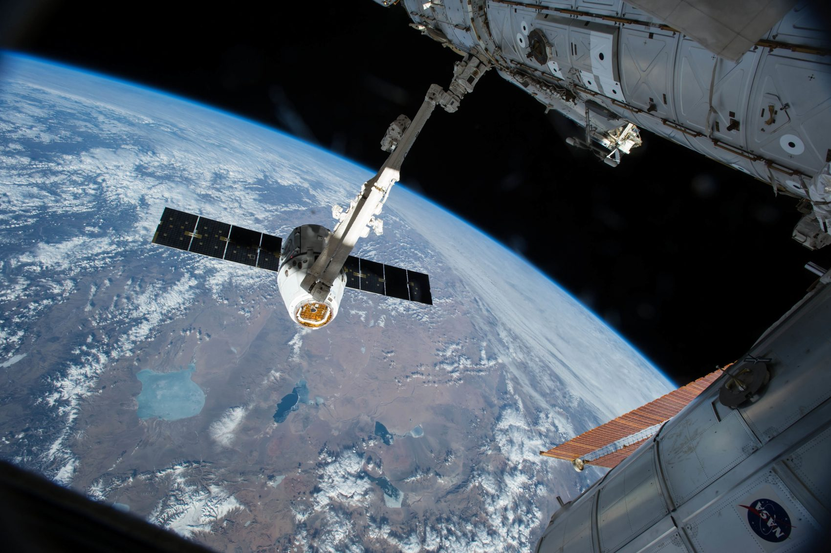 In this April 17, 2015 photo, the Canadarm 2 reaches out to capture the SpaceX Dragon cargo spacecraft for docking to the International Space Station. (NASA/AP)