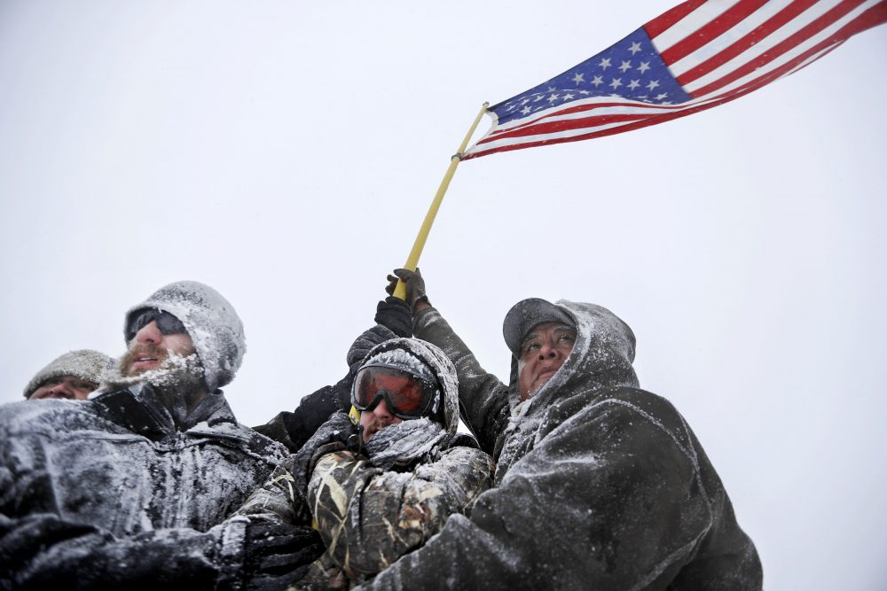Military veterans huddle together to hold a United States flag against strong winds during a march to a closed bridge outside the Oceti Sakowin camp where people have gathered to protest the Dakota Access oil pipeline in Cannon Ball, N.D., Monday, Dec. 5, 2016. (David Goldman/AP)